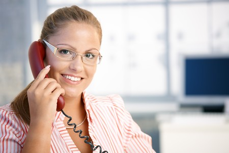 Pretty receptionist working in office, talking on phone, smiling. photo