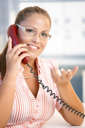 Attractive woman talking on phone in office, gesturing, smiling. photo