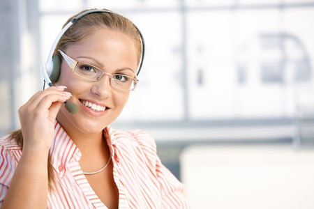 Pretty dispatcher working in office, using headset, smiling. photo