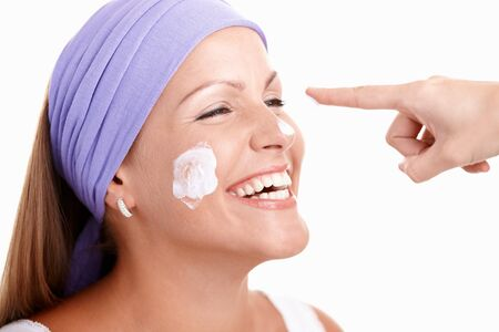 Portrait of attractive young female, applying cream on face, wearing headband, having fun, laughing. Stock Photo - 8121326