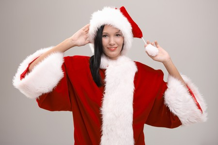 Cheerful young woman wearing huge Santa Claus costume, looking at camera, isolated on gray background. photo