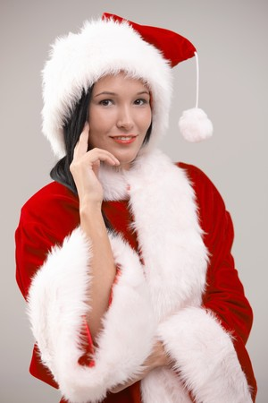 Portrait of happy young woman wearing santa costume, looking at camera, isolated on gray background. photo