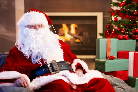 Portrait of Santa Claus sitting by fireplace with Christmas presents all around, looking at camera. photo