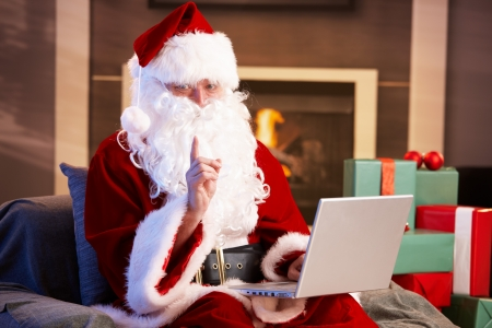 Modern Santa Claus sitting by fireplace using computer computer. photo
