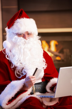 Santa Claus using computer purchasing Christmas presents online paying with credit card. photo