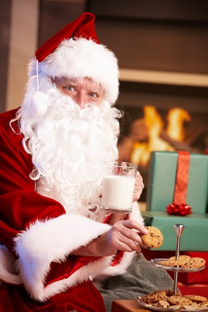 Satisfied Santa Claus sitting at fireplace drinking milk and eating chocolate chip cookies, looking at camera. Stock Photo - 8121645