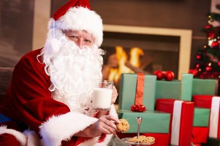 galleta de chocolate: Feliz Pap� Noel sentado en la chimenea beber leche y comer galletas de chispas de chocolate, mirando la c�mara.  Foto de archivo