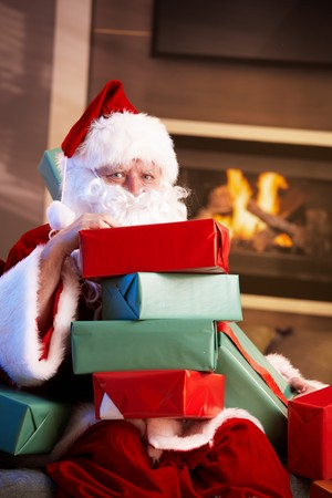 Portrait of Santa Claus sitting by fireplace holding a pile of Christmas presents. photo