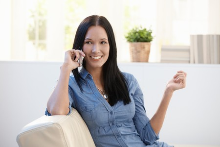 Pretty woman making phone call on couch in living room, smiling. Stock Photo - 8121477