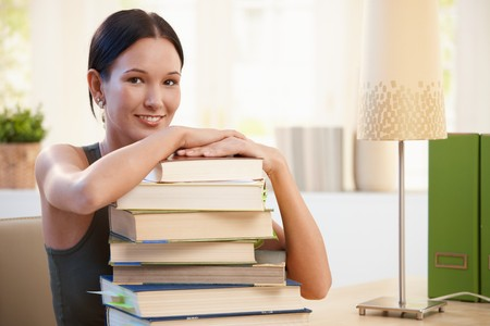 Girl posing with pile of books to learn, putting arms around books, smiling at camera. Stock Photo - 8121491