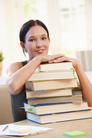Smiling university student girl sitting at desk with pile of books. photo