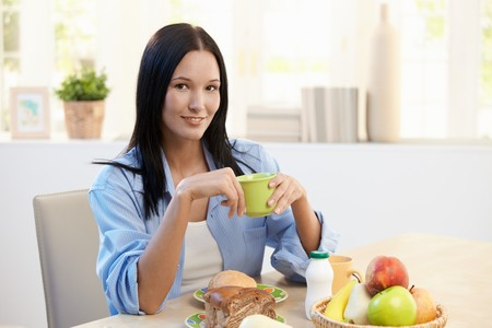 Smiling beautiful woman sitting at breakfast table, holding cup, looking at camera. Stock Photo - 8121485
