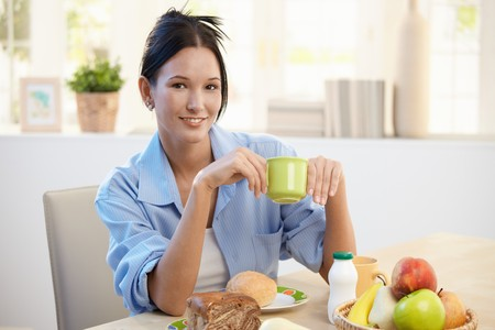 Breakfast portrait of young pretty woman holding coffee cup. Stock Photo - 8121484