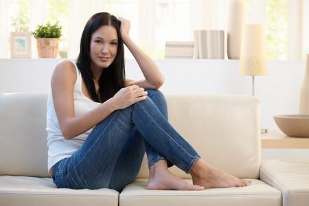 mujeres sentadas: Retrato de mujer bonita posando en sof� en casa, sonriendo a la c�mara.