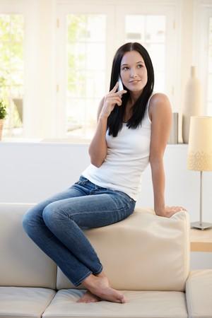 persona llamando: Mujer bonita posando en sof� en casa hablando por tel�fono celular, sonriendo.