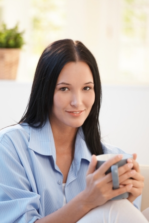 Portrait of young woman having tea, smiling at camera. Stock Photo - 8121514