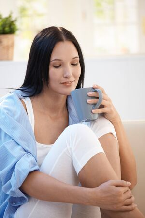 Pretty girl having tea at home, smiling, holding cup. photo