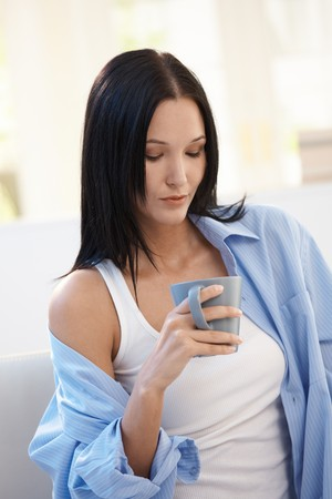 Attractive young woman posing with coffee mug at home. photo