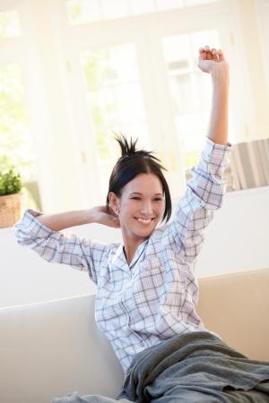 Joyeuse fille portant un pyjama, s'étirant dans la matinée, souriant dans le salon lumineux.