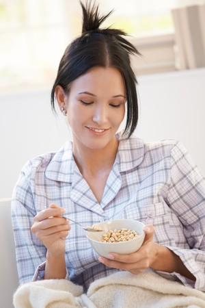 Girl in pyjama having cereal breakfast at home, smiling. photo