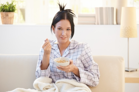 Girl in pyjama having cereal breakfast on couch, smiling at camera. photo