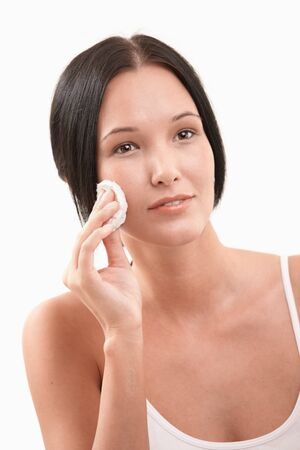 cotton pad: Beautiful young woman cleaning face using cotton pad, smiling. Stock Photo