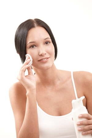 cotton pad: Beautiful woman cleaning face with cotton pad, holding facial cleaning bottle, smiling.