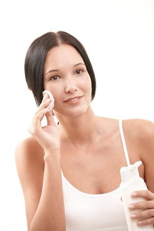pulizia viso: Bella donna pulizia viso con un tampone di cotone, tenendo la bottiglia di pulizia del viso, sorridente. Archivio Fotografico