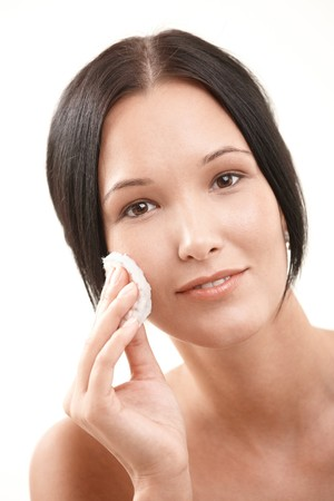 Pretty young woman doing facial cleaning with cotton pad, smiling at camera. photo