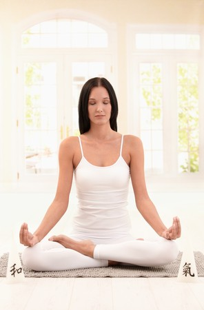 Young woman meditating with closed eyes in bright living room. photo