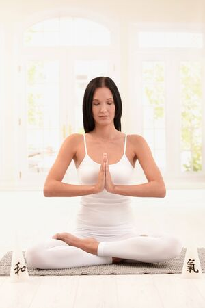 meditating woman: Young woman wearing white doing yoga exercise with closed eyes.