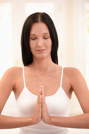 Portrait of young woman doing meditation with closed eyes. photo