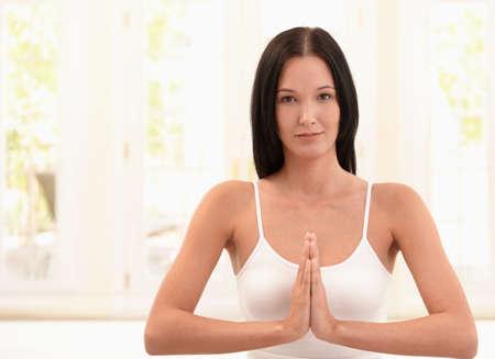 Happy woman exercising meditation, smiling at camera, copyspace. photo