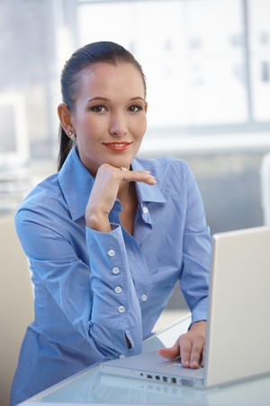 Portrait of attractive office girl sitting at desk, smiling at camera. photo