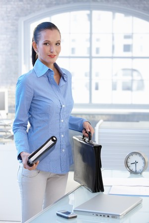 Smiling businesswoman standing in office holding briefcase and calendar. photo
