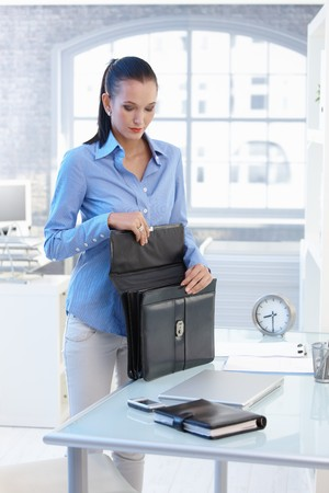 Businesswoman opening briefcase, standing at office desk. Stock Photo - 8121625
