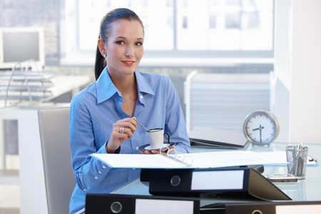 Smiling businesswoman having coffee break in office, looking at camera. photo