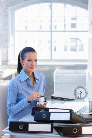 Portrait of smiling young businesswoman having coffee sitting at desk in office. photo