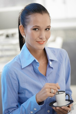 Portrait of pretty office worker girl having coffee, smiling at camera. photo
