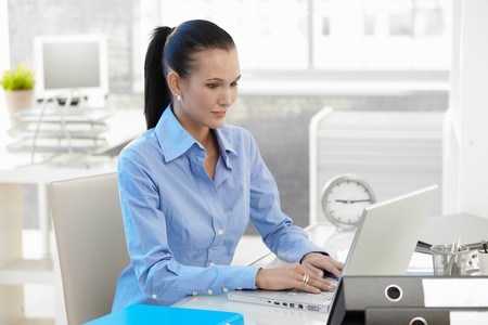 Office girl working on laptop computer at desk, looking at monitor, smiling. Stock Photo - 8121515