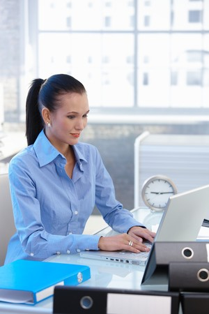 Young businesswoman working on laptop computer at office desk, smiling. Stock Photo - 8121631