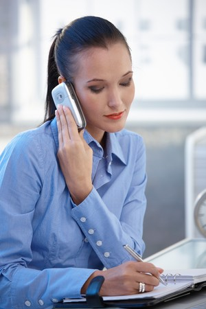 Businesswoman taking notes while on mobile phone call, listening. photo