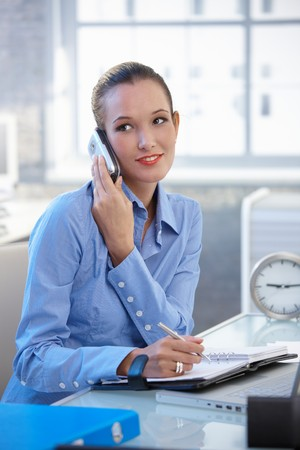 Smiling businesswoman talking on cellphone and writing into notebook at office desk. photo