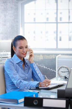 Cheerful businesswoman on landline call, taking notes, smiling. photo