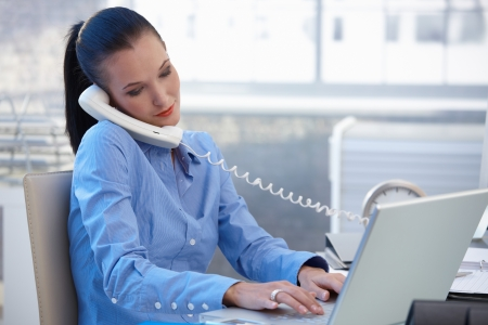 calling on phone: Busy office worker girl taking landline phone call while typing on laptop computer. Stock Photo
