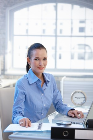 Smiling office worker girl busy at desk with laptop computer and documents. Stock Photo - 8121503