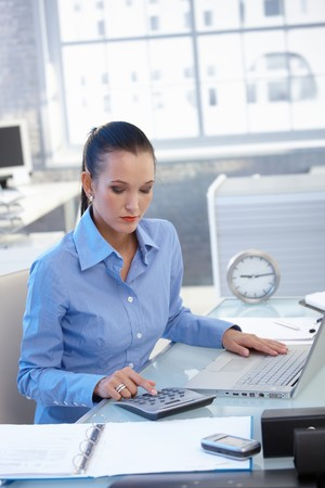 Businesswoman busy working at desk with calculator, doing financial task. Stock Photo - 8121626