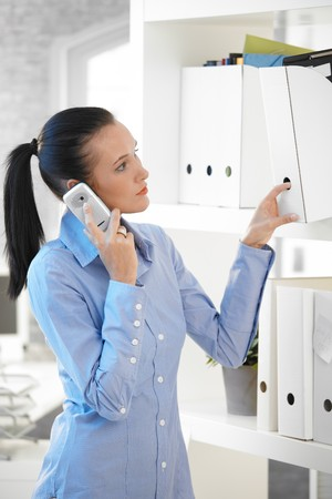 Girl in office taking folder from shelf while on mobile phone call. Stock Photo - 8121667