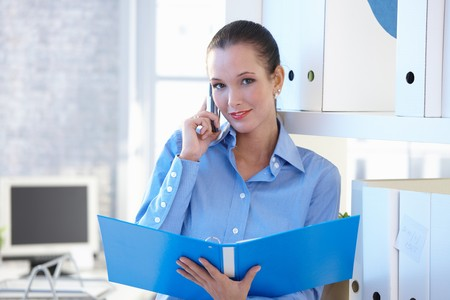 Young smiling attractive assistant on mobile phone call, holding folder in office, smiling at camera. photo