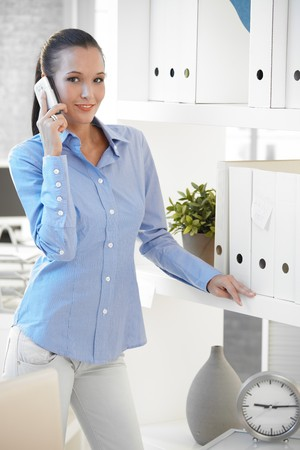 Pretty assistant talking on cellphone, standing in office by folders, smiling, looking at camera. photo